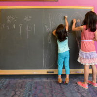 Two young kids drawing on a large chalkboard.