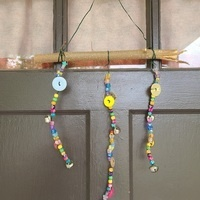 a wind chime made of a large stick, twine and beads