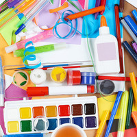 craft supplies including paint, glue, markers, and paper laid out on a table