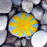 a painted rock featuring a yellow sun on a blue background