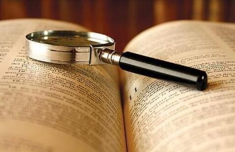 Magnifying glass sitting atop an open book.
