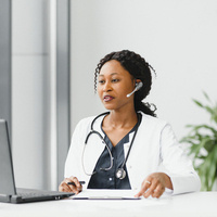 A Black female-presenting nurse with headset, stethoscope, and laptop.