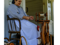 A lady using a spinning wheel on the museum grounds.