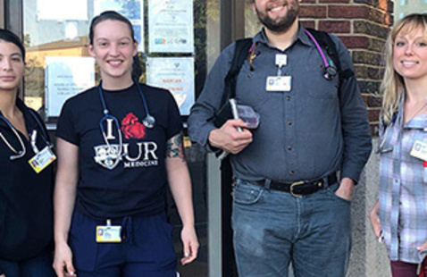 Four people participating in the Street Outreach program wear casual clothes with stethoscopes over their necks.