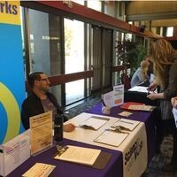 Vendor and students at a career fair table