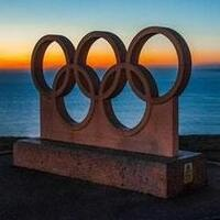 five Olympic rings carved into stone, in front of a body of water at sunset
