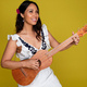 Sonia De Los Santos playing guitar in front of a yellow background