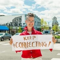 """Author Ginger Johnson holding a sign that says """"Keep Connecting"""""""