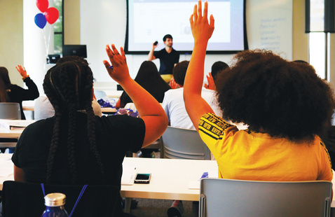 Two students raise their hands in the foreground with a lecturer speaking in the background