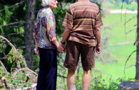 Older couple holding hands while standing in a forest