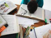 person with head down at desk- papers all over