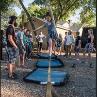A student walking a slack line while others watch