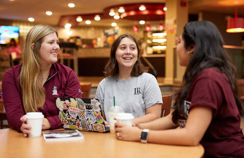 Three students sitting at table with coffee at Joe's Coffee on campus