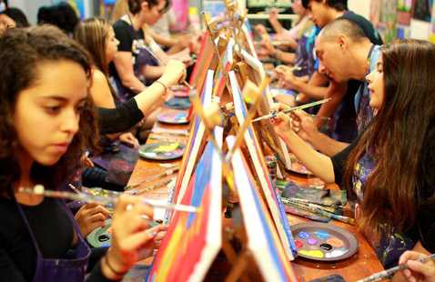 Large group of people painting on canvases