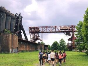 Group of students walking on a path near rusted steel equipment