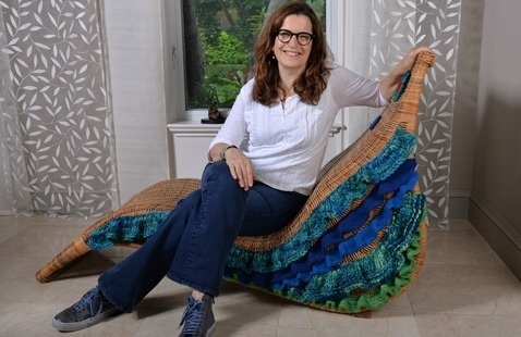 Artist Evelyn Politzer sitting on one of her creations.