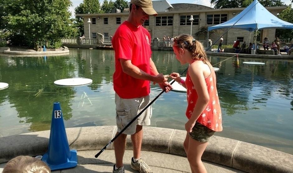 Volunteer Mark helping kid at Pond 2019