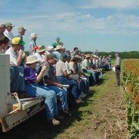 A group sits on a flatbed truck to listen to a field day presentation.