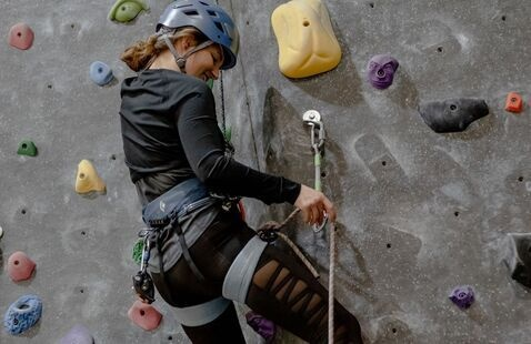 Woman practicing clipping in while climbing in a UREC Outdoors lead clinic.