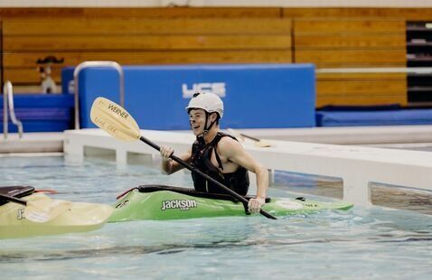Man sitting in a whitewater kayak practicing paddling and whitewater roll skills.