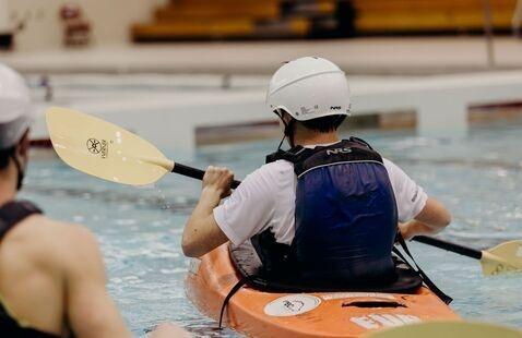 Man sitting in a whitewater kayak practicing his paddling skills.