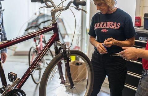 A bike mechanic is helping a participant fix their bike.