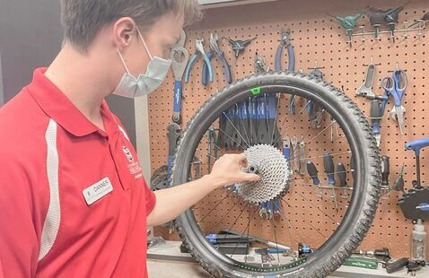 Bike mechanic is spending time inspecting a bike wheel to be fixed.