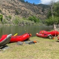 Red rafts sitting next to a river