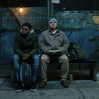 A young man sits on a bus bench next to a DeafBlind man. They are both wearing jackets. The DeafBlind man is wearing a toboggan and holding a notebook.