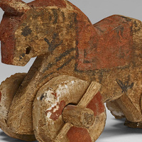 Horse-shaped toy with orange paint and wooden wheels. © The Trustees of the British Museum