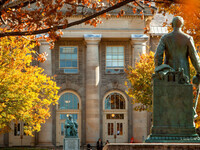 Statues of AD White and Ezra Cornell facing one another across the Arts Quad in fall