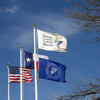 This image has 4 flags on it that are flying in front of a blue sky. The flags are the American Flag, the Texas Flag, the TCC flag and the Achieving the Dream flag.