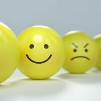 There are 2 yellow balls with faces on them. One is smiling and one has an angry face.