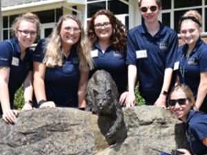 A group of Peer Leaders gathered around the statue of Bruiser the Bobcat