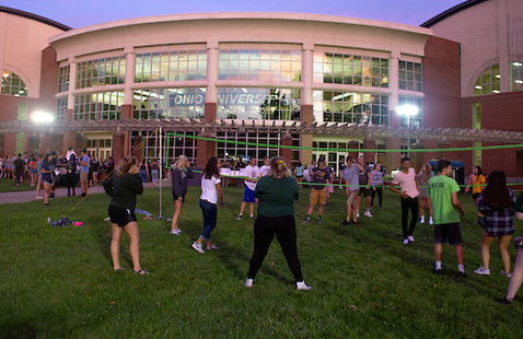 Students playing volleyball on the front lawn of the Ping Center