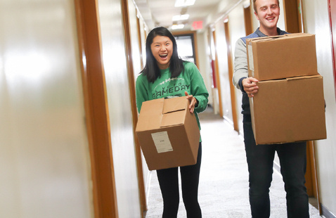 two students carrying boxes down a residence hall hallway