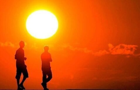 Silhouettes standing in front of a large sun