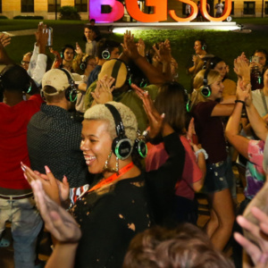 Silent disco - students dancing outside with headphones on