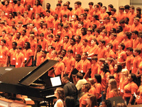 Choral members singing in an auditorium with a piano in the center left