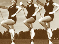 A sepia toned image of three female members of The Pride of Mississippi Marching Band