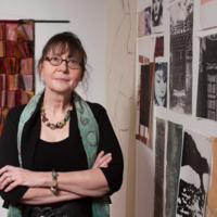 Photo portrait of Anne Beidler, a dark haired white woman with glasses, standing with arms crossed and a half-smile on her face and printed artworks in the background