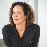 photo of Aminatta Forna, a brown skinned woman with kinky curly hair, smiling with a smirk at the camera and wearing a black shirt