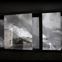 photo of projections of clouds and buildings on a gallery wall