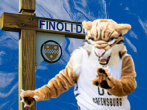 Bruiser the Bobcat dancing in front of the Finoli Drive street sign