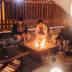 male students sitting around a fire table and enjoying the fire