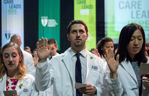 Newly coated students recite the Osteopathic Pledge of Commitment to the audience