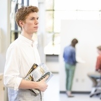 Student holding textbooks in a classroom.