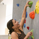 This is a photo of a girl with brown hair climbing on the climbing wall at UREC. Her upper body is in frame; she smiles as she grabs two green holds on the wall.