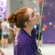 This is a photo of a staff member with red hair's profile. She is holding the bottom of the rope and looking up at the rock climbing wall. The rope is taught, so one can assume that she is holding the rope for someone who is climbing up the tall rock wall.