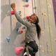 This is a photo of a girl climbing with the ropes. She is on the tall climbing wall holding onto the holds. She wears a grey jacket and black leggings with a white stripe. Her hair is pulled back with a headband and ponytail. She is smiling down at the people on the ground, though she is the only one in frame.